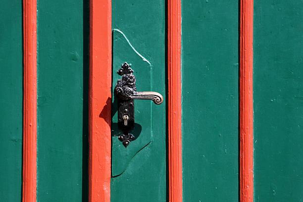 griff auf einem gestreiften rot-grüne hölzerne tür - beschläge türen stock-fotos und bilder
