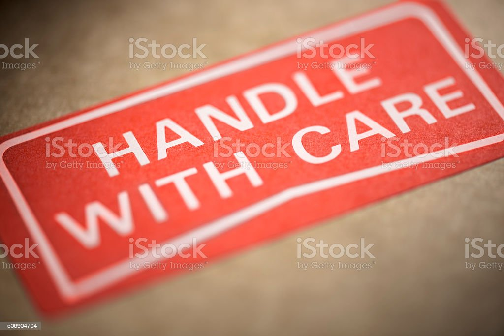 A Handle With Care label is stuck to the outside of a brown cardboard...