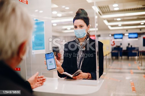 Senior man traveling in the times of the coronavirus pandemic. He is checking in on the flight as the handling agent is looking at the covid passport.