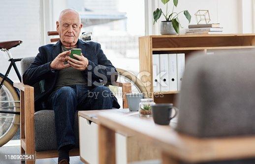 Shot of a senior businessman using a cellphone in an office