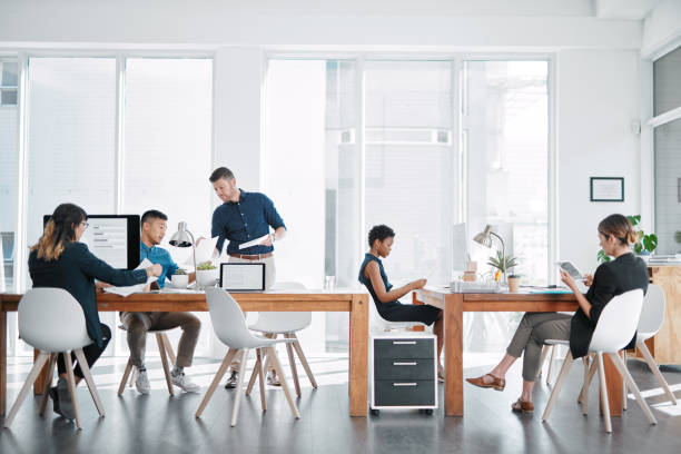 Handling business like the go getters they are Shot of a team of businesspeople working together in a modern office coworking stock pictures, royalty-free photos & images