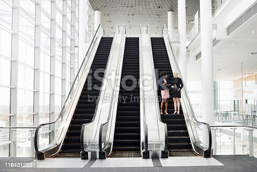 Full length shot of two businesswomen having a discussion while coming down an escalator in the workplace