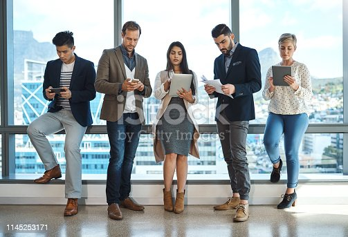 Full length shot of a diverse group of businesspeople using wireless technology in an office