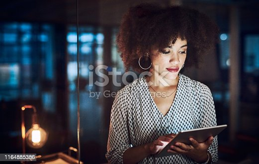 Shot of a beautiful young businesswoman using a digital tablet while working late in her office