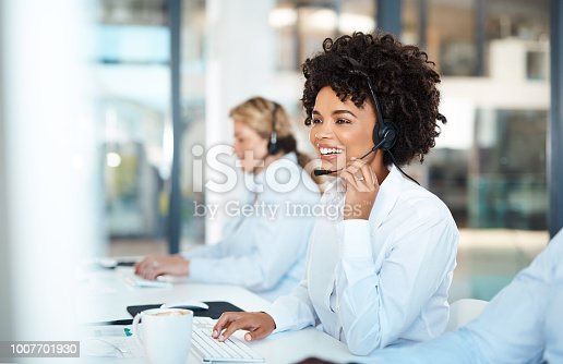 Shot of a young call centre agent working alongside her colleagues in an office