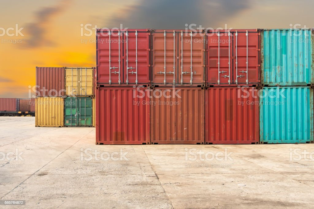 Handling stack of container shipping on twilight scene. stock photo
