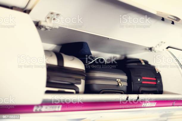 Handluggage Compartment With Suitcases In Airplane Carryon Luggage On Top Shelf Of Plane Travel Concept With Copy Space Stock Photo - Download Image Now