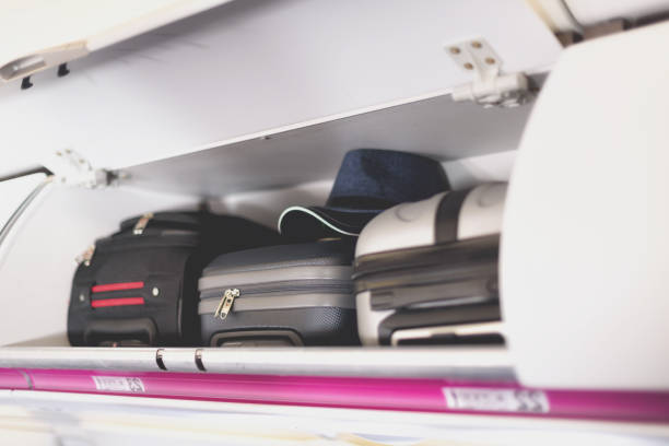 Hand-luggage compartment with suitcases in airplane. Carry-on luggage on top shelf of plane. Travel concept with copy space Hand-luggage compartment with suitcases in airplane. Carry-on luggage on top shelf of plane. Travel concept with copy space. carry on luggage stock pictures, royalty-free photos & images