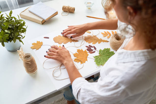 Handmade Autumn Crafts High angle portrait of young woman making handmade autumn decoration using yellow eaves hobbies stock pictures, royalty-free photos & images