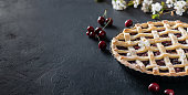 Handmade baking. Cherry pie on a black background,  place for text.