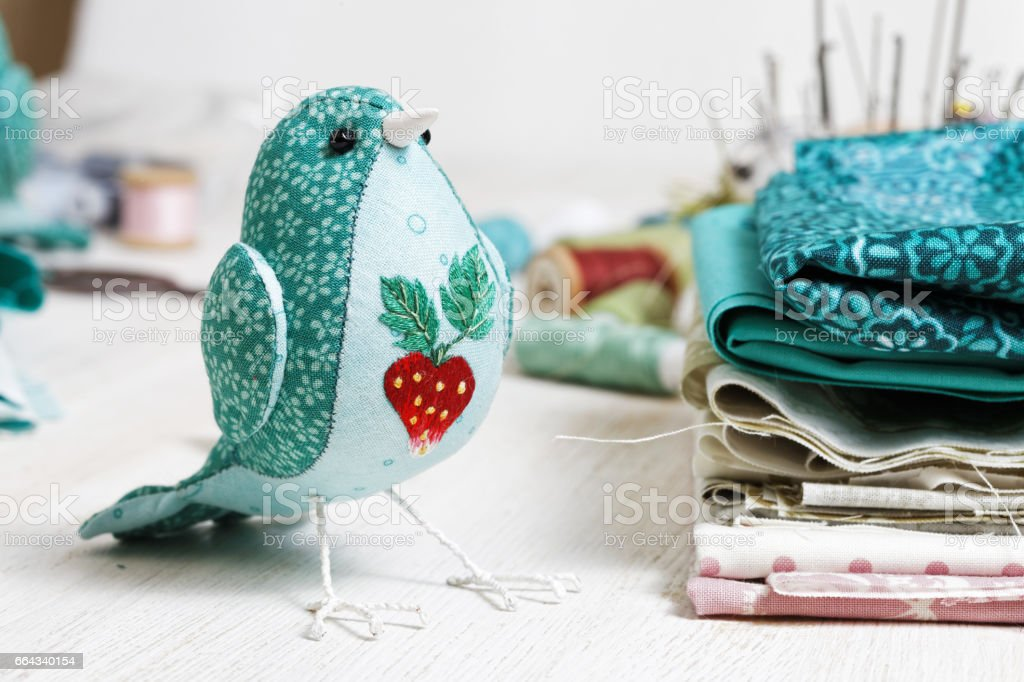Handmade bird sewed from a cloth stands on a white wooden table surrounded by handicraft  materials. stock photo