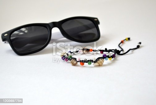 Handmade bracelet made of multi-colored beads and Vietnamese seashells of the South China Sea, isolated on white background and blurred sunglasses