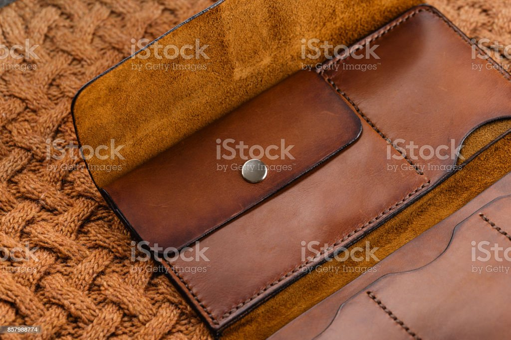 Handmade brown leather empty opened wallet on red knitted background