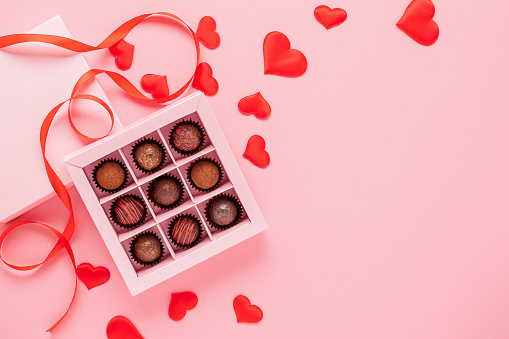 Handmade chocolates truffle in a box on a pink background with valentines. Valentines day concept festive food gifts.