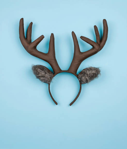 Handmade Christmas reindeer ears and antlers on bright blue background stock photo