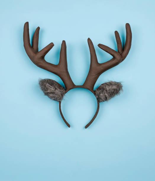 handgemachte weihnachten rentier ohren und geweih auf leuchtend blauem hintergrund - geweih stock-fotos und bilder