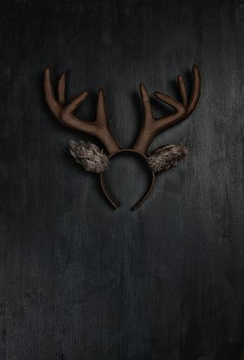istock Handmade Christmas reindeer ears and antlers on dark background 855195566