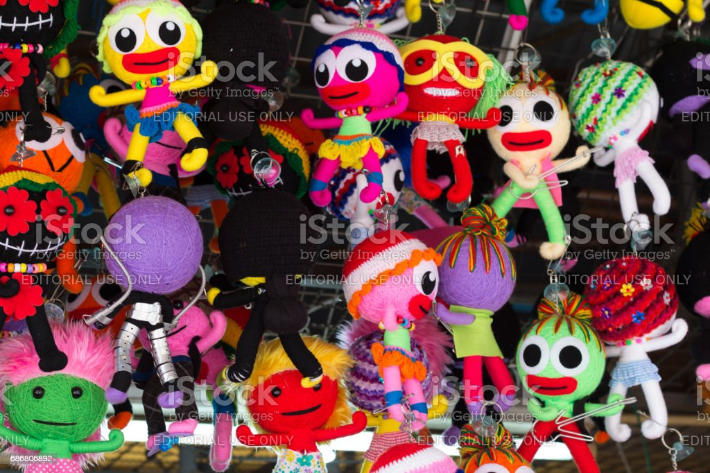 handmade colorful fabric doll-shape key chain hanging on the rack stock photo