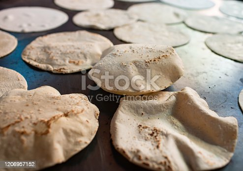 Handmade corn (maize) tortillas puffing up while cooking on a griddle at a mexican market.
