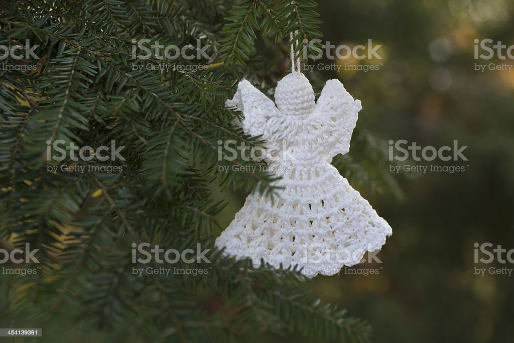 Handmade Crochet Christmas Angel ornament on an outdoor tree stock photo