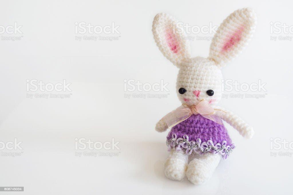 Muñeca de ganchillo hecho a mano. Muñeca de conejo lindo sobre fondo blanco. Amigurumi. Creativa y artesanal juguete. - foto de stock