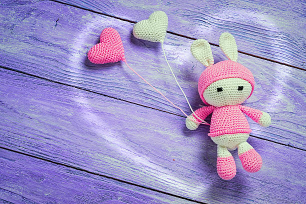 handmade crochet rabbit toy with heart shape baloons - nähpuppen stock-fotos und bilder
