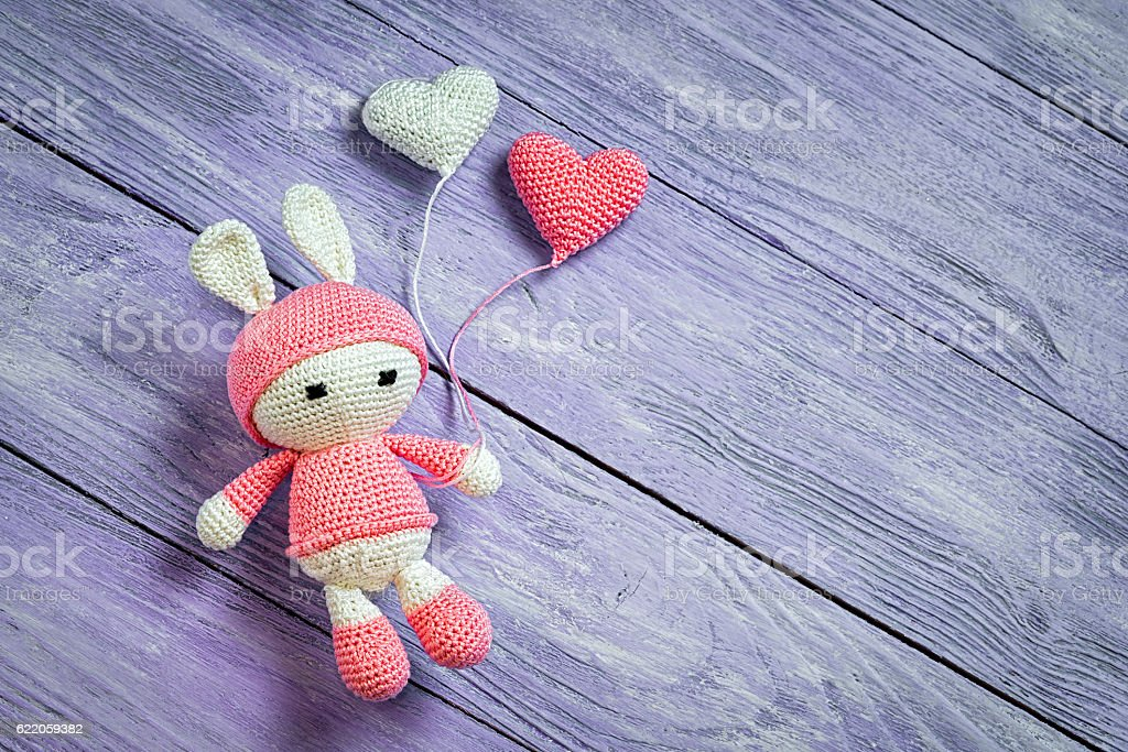Handmade crochet rabbit toy with two heart balls. stock photo