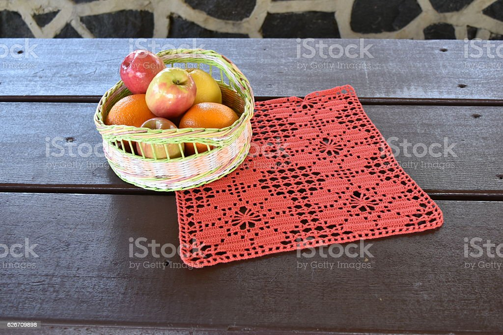 Handmade crochet red doily over wooden background stock photo