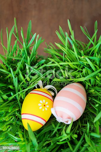 930928526 istock photo Handmade Easter eggs and fresh green grass on dark wooden background. Top view 930928602