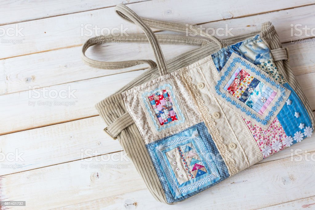 handmade, fashion, accessories concept -flatlay of charming women's bag made of velveteen and front part sewing in technique patchwork with colorful ornate snippets. it has two straps, lace and button royalty-free stock photo
