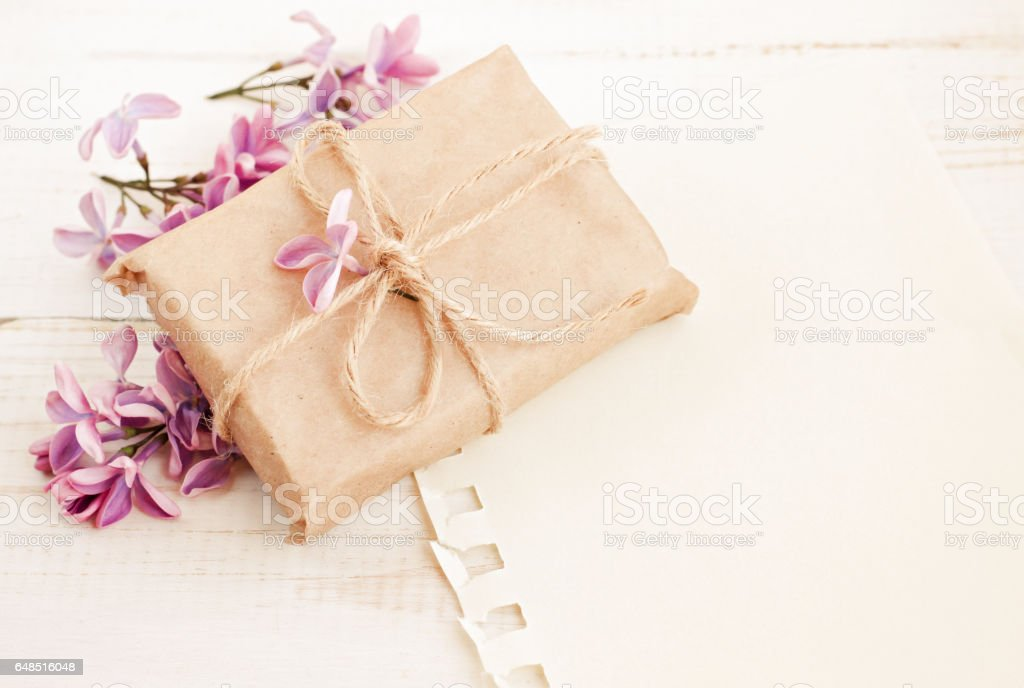 Handmade gift box in craft paper with twine, fresh spring lilac blossom empty message background. Light soft dreamy colors. Birthday Stock Photo