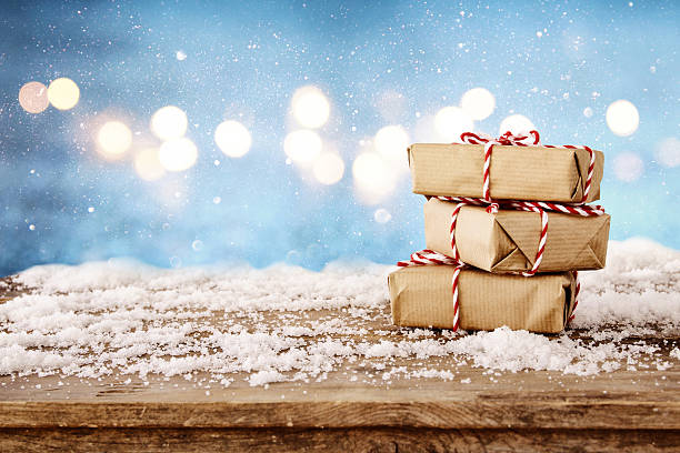 handmade gift boxes over snowy wooden table - foto stock