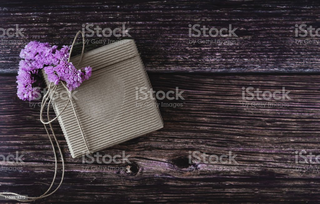 Handmade gift concept. Craft paper recycle gift box with flowers on...