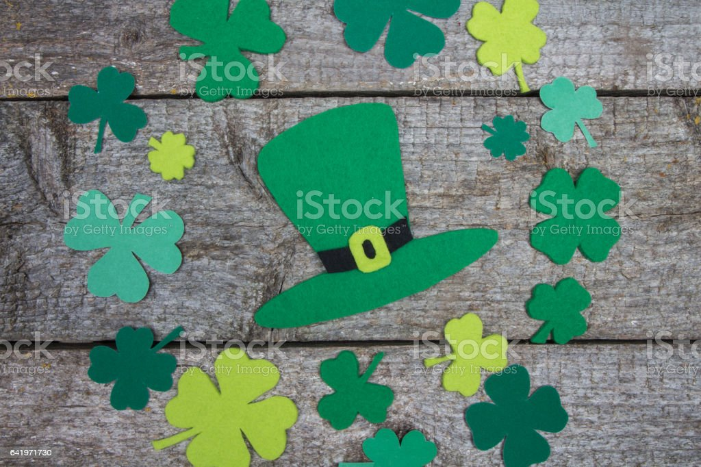 Handmade hat Patrick and range of leaf clover on table. stock photo