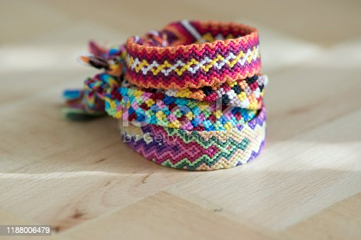 Handmade homemade colorful natural woven bracelets of friendship isolated on light blue background, pile of colorful fashion handcraft on wooden background