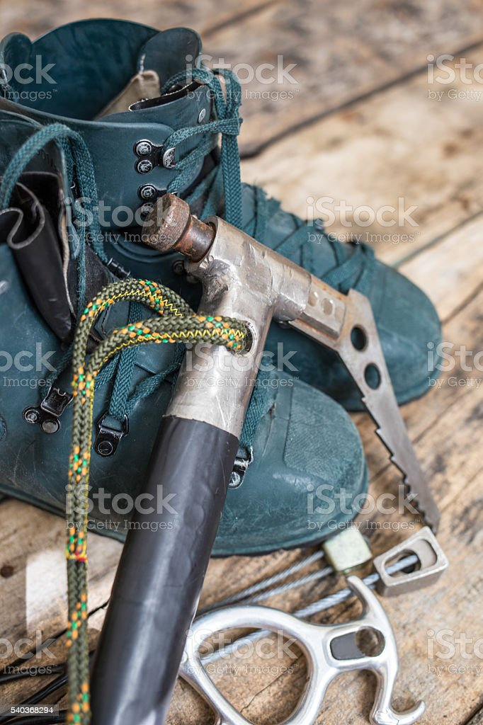 Handmade ice axe with old boots on wood background stock photo