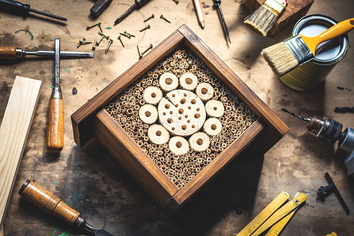 Handmade insect hotel or house on wooden table at workshop