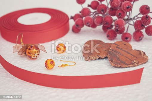 1074436306istockphoto Handmade Jewelry, DIY close up in red and brown. Jewelry designer workplace. Materials for creation handmade earrings with amber and wire. fashion femininity workspace 1056374422