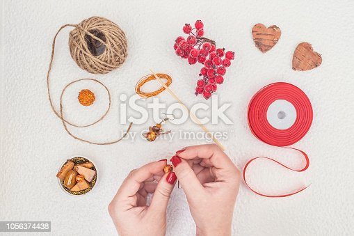 1074436306istockphoto Handmade Jewelry, DIY flat lay in red and brown. Jewelry designer workplace. Woman hands making handmade earrings with amber. Freelance fashion femininity workspace in flat lay style. 1056374438