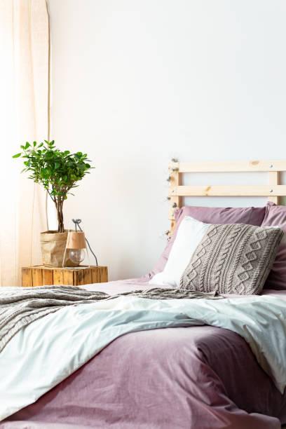 handgefertigte lampen und frischen pflanze stehend auf holz nachttisch neben bett mit lila bettwäsche und stricken kissen in hellen schlafzimmer innenraum - lila, grün, schlafzimmer stock-fotos und bilder