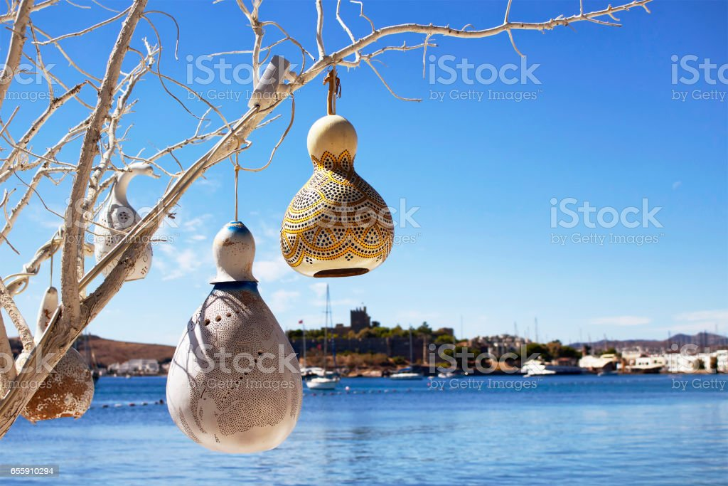 Handmade lamps made of water pumpkin (Calabash) at seaside of Bodrum city in Turkey. Yachts, Aegean sea and Bodrum castle are in the background. These lighting is used in the region for decoration. stock photo