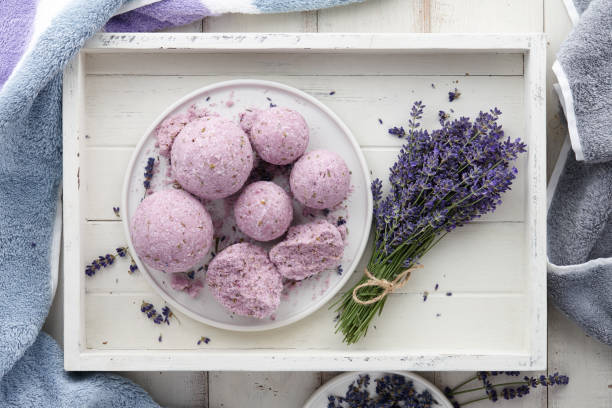 Handmade lavender bath bombs and flowers in white tray Handmade lavender bath bombs and lavender flowers in white tray, top view bathtub stock pictures, royalty-free photos & images