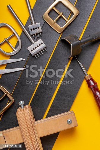 istock Handmade leather craft tools, belt buckle and black leather straps on yellow background 1141559913