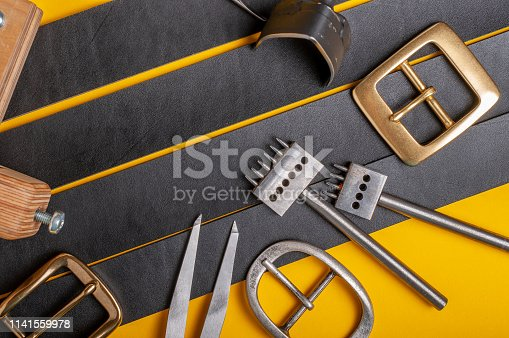 istock Handmade leather craft tools, belt buckle and black leather straps on yellow background 1141559978