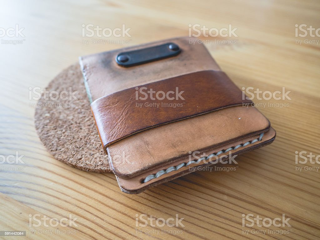 Grunged and dirty leather wallet on wooden table.