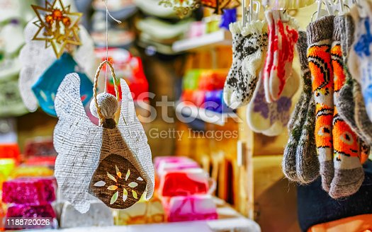 Angel and Knitted souvenirs in stalls at Christmas market in Riga of Latvia winter. Europe. Street Xmas and holiday fair in European city or town. Advent Decoration and Stalls on Bazaar