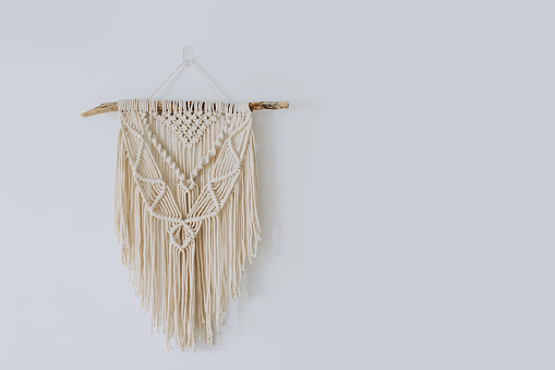 Handmade stylish cotton macrame decoration hanging on a white empty wall. Copy space.