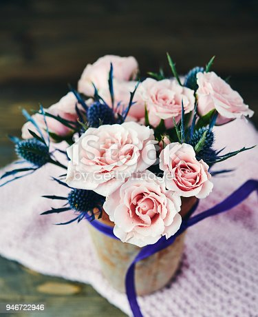 Handmade Mother's Day bouquet with pink roses in rustic pottery vase