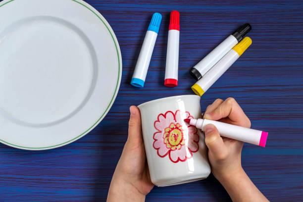 handgefertigte gemälde an geschirr marker für keramik. schritt 3 - handbemalte teller stock-fotos und bilder