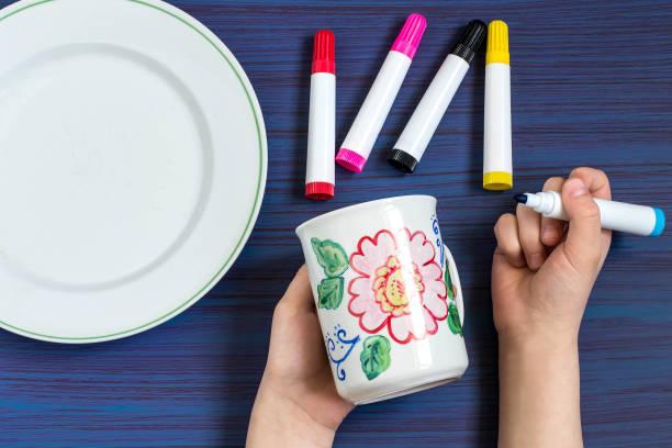 Handmade painting on crockery markers for ceramics. Step 4 stock photo